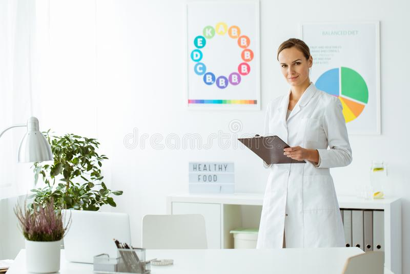 Berufsernährungswissenschaftler in der weißen Uniform lizenzfreie stockfotos