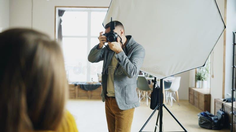 Berufsfotograf, der Fotos des Modells auf der Digitalkamera arbeitet im Fotostudio macht stockfotografie