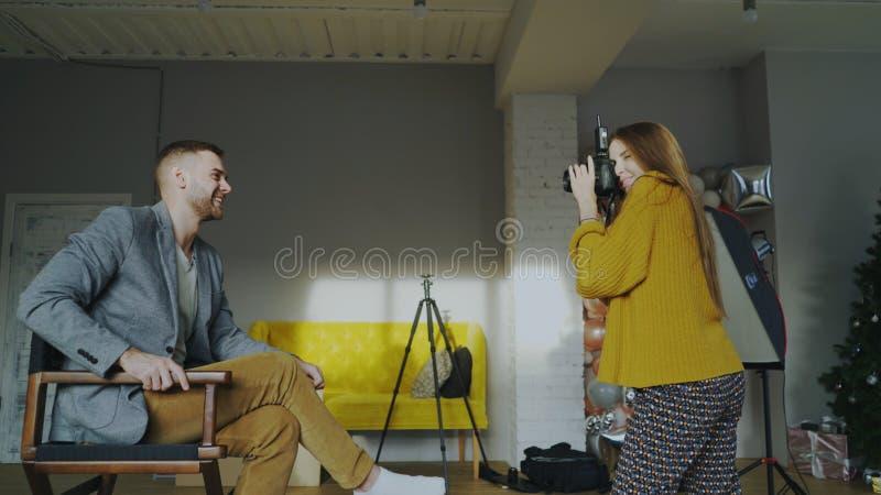 Berufsfotograffrau, die Foto des Geschäftsmannmodellmädchens mit Digitalkamera im Studio macht lizenzfreie stockfotografie