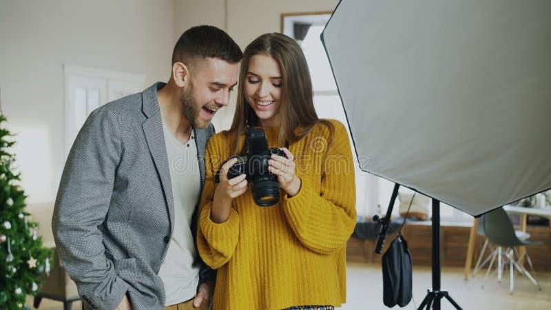 Berufsfotograffrau, die zuhause dem attraktiven vorbildlichen Mann Fotos auf Digitalkamera im Fotostudio zeigt lizenzfreie stockbilder