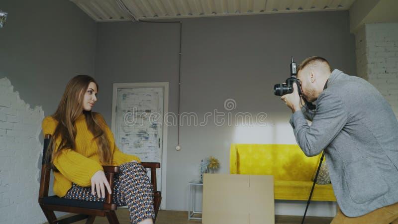 Berufsfotografmann, der Foto des schönen vorbildlichen Mädchens mit Digitalkamera im Studio macht stockbilder