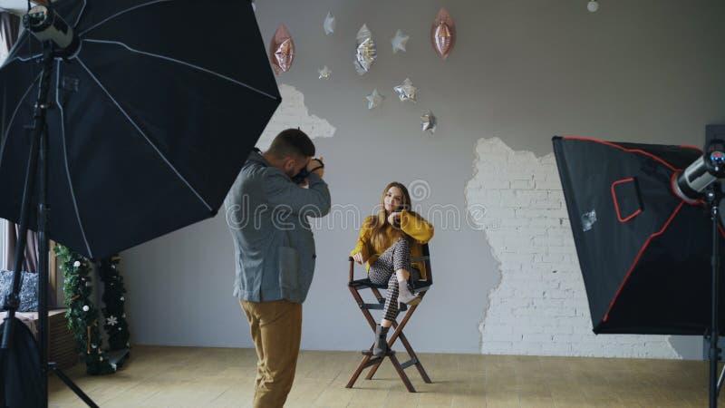 Berufsfotografmann, der Foto des schönen vorbildlichen Mädchens mit Digitalkamera im Studio macht lizenzfreies stockbild
