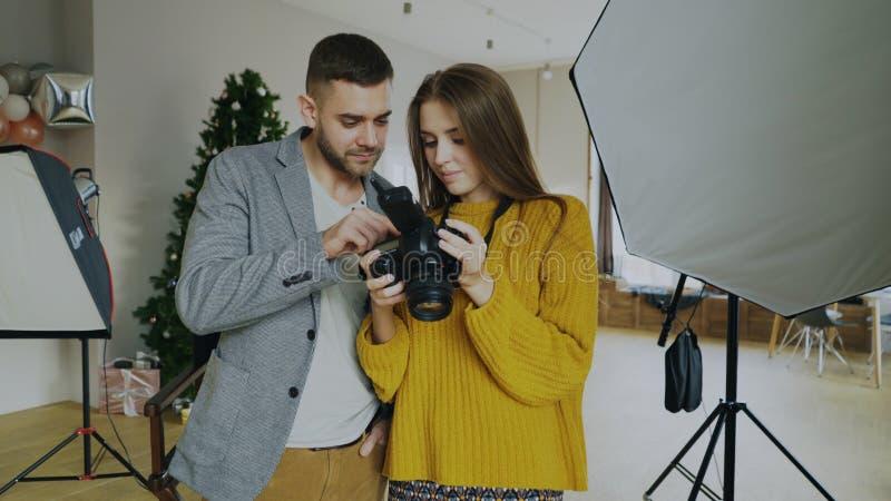 Berufsfotografmann, der zuhause dem schönen vorbildlichen Mädchen Fotos auf Digitalkamera im Fotostudio zeigt stockfotos
