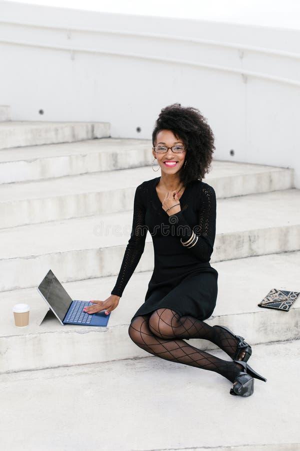 Berufsfrau der stilvollen jungen Afrofrisur unter Verwendung der Tablette stockfotografie