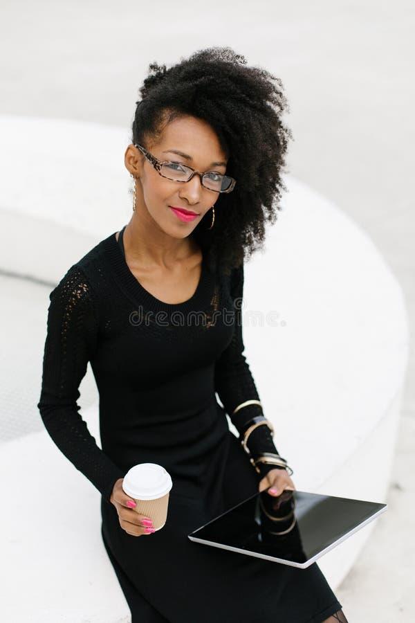 Berufsfrau der stilvollen jungen Afrofrisur unter Verwendung der Tablette lizenzfreie stockfotos