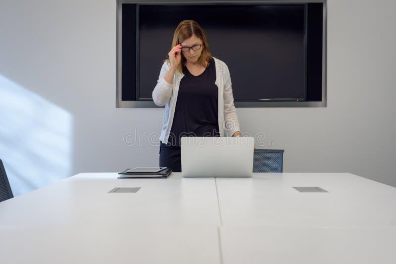 Berufsfrau, die für das Treffen im Konferenzsaal sich vorbereitet lizenzfreies stockbild
