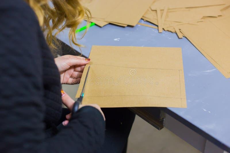 Berufsfrauendekorateur, Designer, der mit Kraftpapier arbeitet stockfotos
