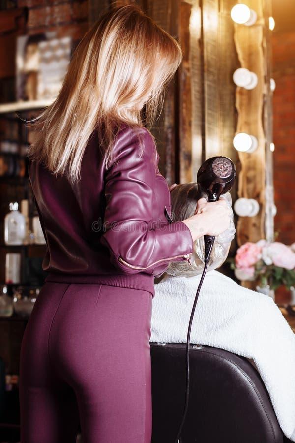 Berufsfriseur, der hairdryer während Haar anredet ihren weiblichen Kunden verwendet Schöne junge Frau, die einen neuen Haarschnit lizenzfreie stockfotos
