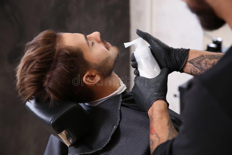 Berufsfriseur, der Talkum verwendet, um die Haut des Kunden nachdem dem Rasieren zu beruhigen stockfoto