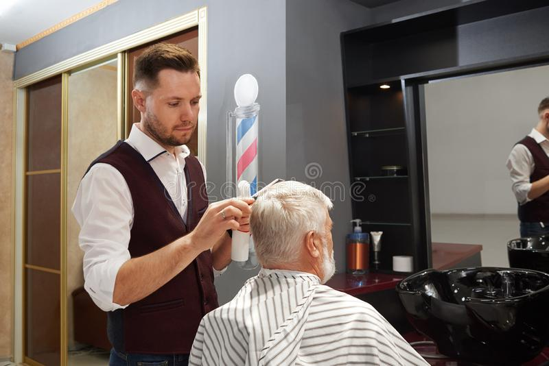 Berufsfriseurpflegenmann ` s Haar im Friseursalon lizenzfreies stockfoto