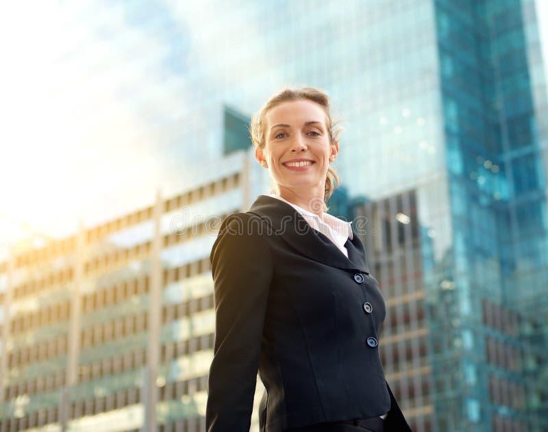 Berufsgeschäftsfrau, die draußen in der Stadt lächelt stockfotografie