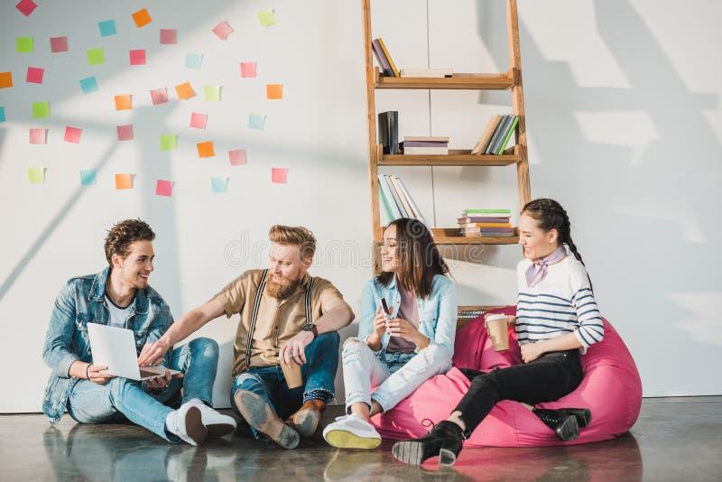 Berufsgeschäftskollegemänner und -frauen, die auf Boden und dem Arbeiten sitzen stockbild