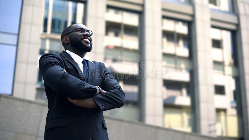 Berufsgeschäftsmann, der oben, Kreuzungsarme, motiviert nach Karrierewachstum sucht stockbild