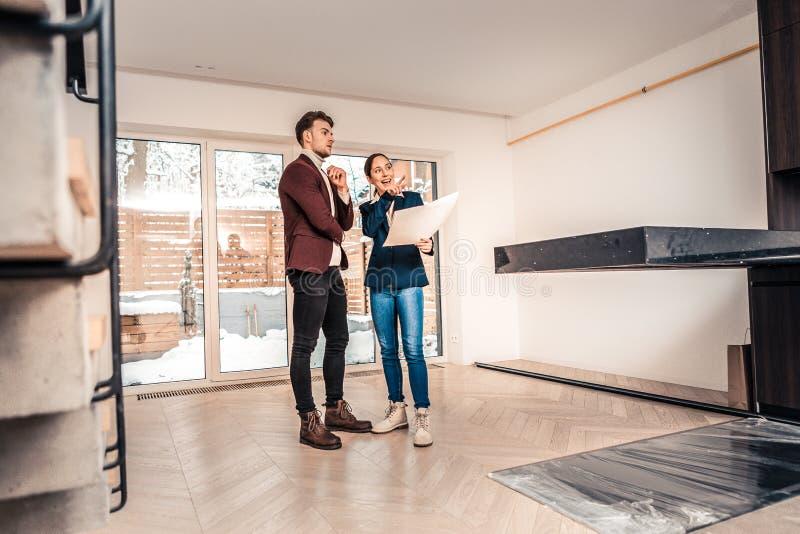 Berufsgrundstücksmakler, der über Eigenschaften des Hauses spricht lizenzfreie stockbilder