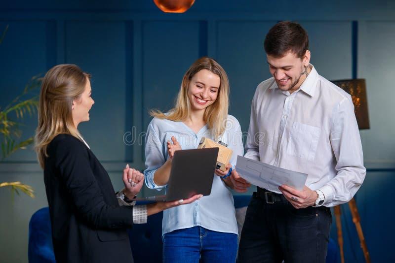 Berufsgrundstücksmakler, Designervertretungsplan des zukünftigen Entwurfs auf dem Laptop zu den Paaren von Kunden lizenzfreies stockbild