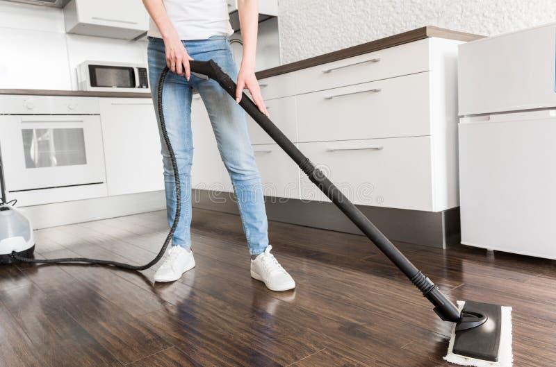 Berufshauptreinigungsservice Frau wäscht den Boden mit einem Dampfmop lizenzfreies stockbild