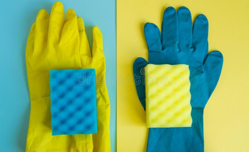 Berufshausreinigungskonzept, Frühjahrsputzzusätze, zwei Paare der Gummihandschuhe und Schwämme auf doppeltem gelb-Blauem lizenzfreies stockbild