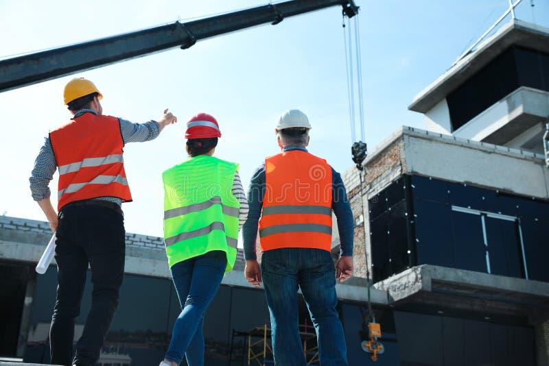 Berufsingenieure in der Schutzausrüstung an der Baustelle lizenzfreie stockfotos