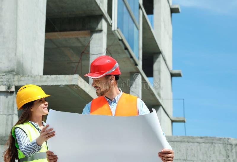 Berufsingenieure in der Schutzausrüstung mit dem Entwurf an der Baustelle stockbilder