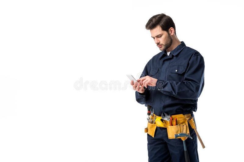 Berufsklempner mit Werkzeuggurt unter Verwendung des Smartphone stockbilder