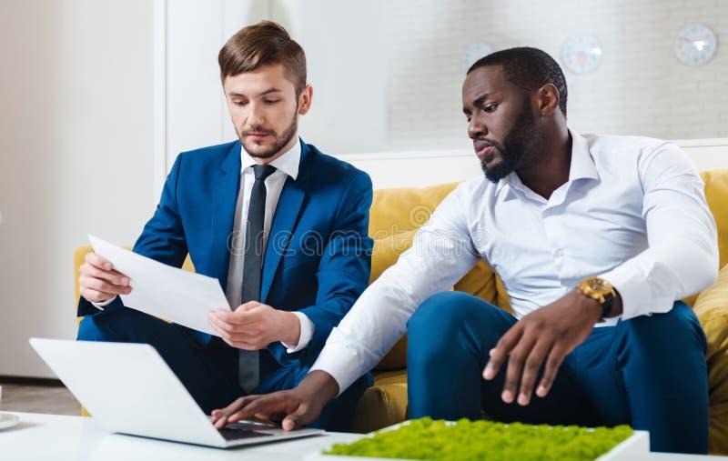 Berufskollegen, die O die Couch sitzen stockfotografie