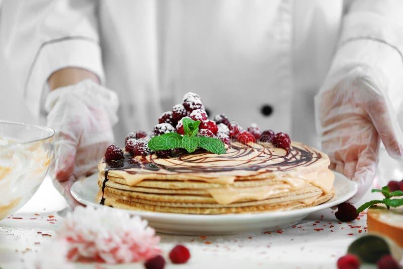Berufskonditor, der köstlichen Kuchen hält lizenzfreie stockfotografie