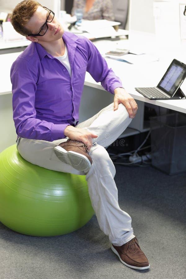 Berufskrankheitsverhinderung - Mann auf dem Gymnastikball, der Bruch für Übung hat lizenzfreie stockfotos