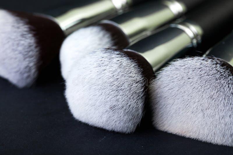 Berufsmake-upbürsten auf einem schwarzen Hintergrund, natürlicher Stoff lizenzfreies stockfoto
