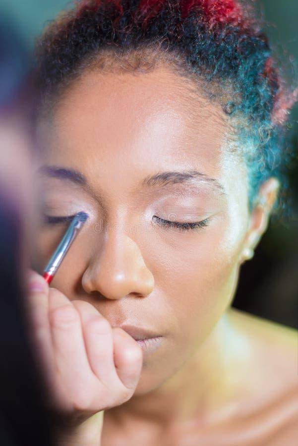 Berufsmake-upmaskenbildner Make-up an einer dunkelhäutigen Frau anwenden stockfoto