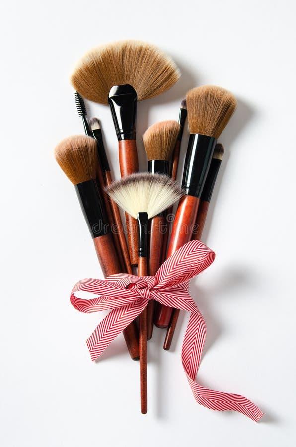 Berufsmake-upwerkzeugbürsten auf einem rosa Pastellhintergrund Zeitschriften, Social Media Beschneidungspfad eingeschlossen Flach stockfoto