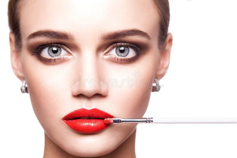 Berufsmaskenbildner wendet Make-up für schöne junge Frau mit blauen Augen und hellbrauner Frisuren- und perfekterhaut an stockfotografie