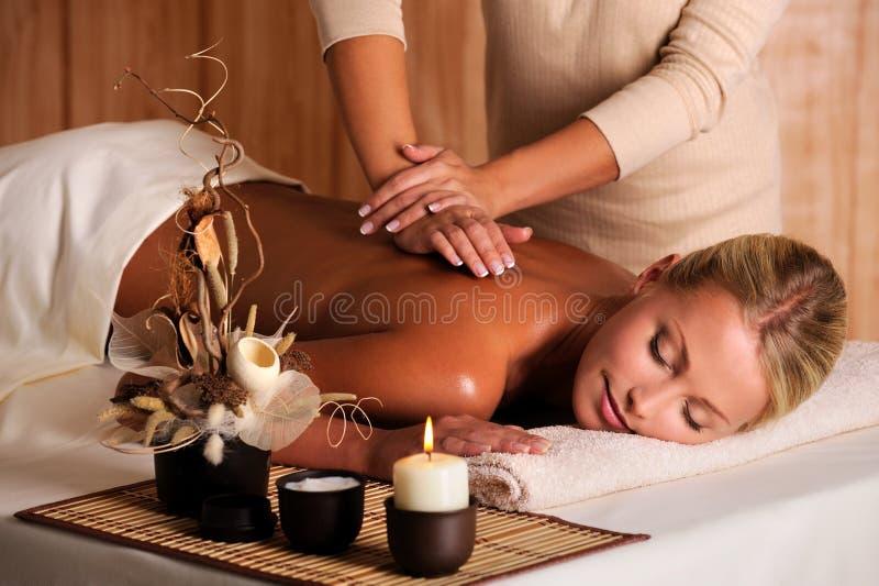 Berufsmasseur, der Massage der Fraurückseite tut stockfotografie