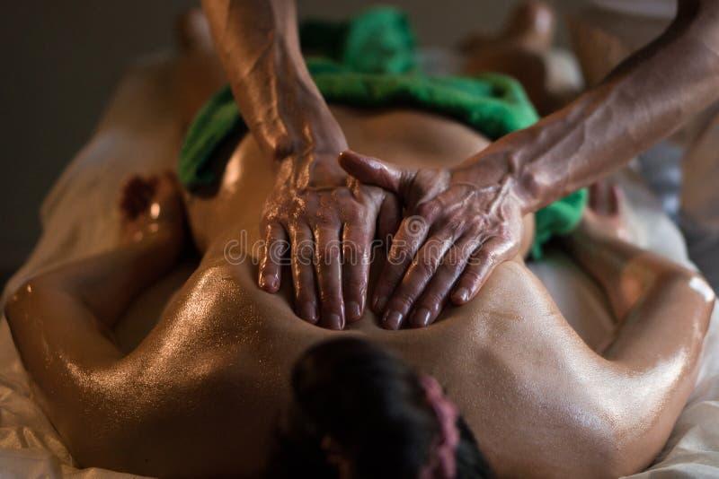 Berufsmasseur, der Tiefengewebe geölte Massage ein Mädchen an der Ayurveda-Massage-Sitzung antut lizenzfreie stockbilder