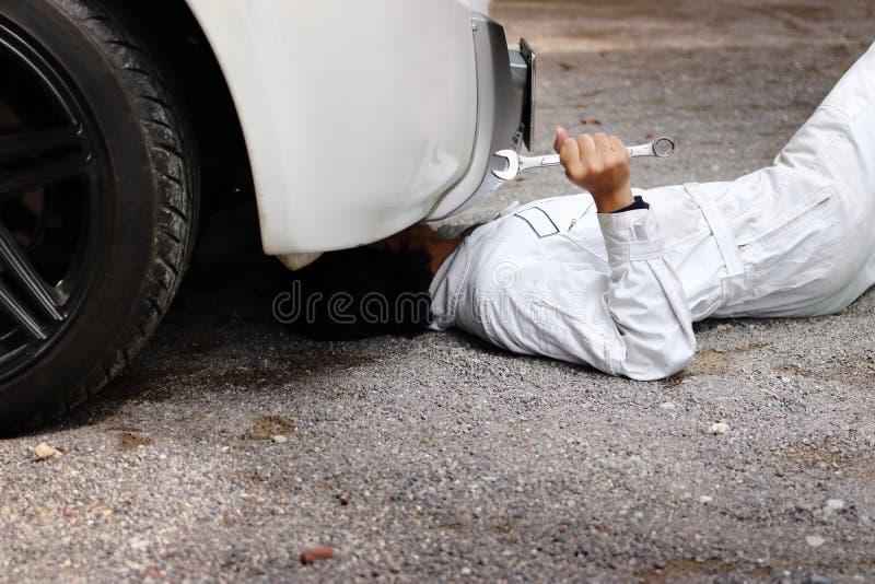 Berufsmechaniker in der weißen Uniform, die sich hinlegt und unter Auto regelt Hübscher lächelnder Mechaniker lizenzfreies stockbild