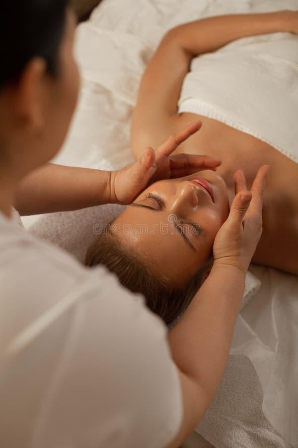 Berufsmeister unter Verwendung der speziellen Bewegungen während der Gesichtsmassage stockbild