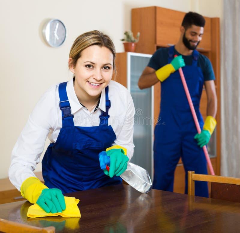 Berufspaare in der einheitlichen Reinigung am inländischen Innenraum lizenzfreie stockfotos