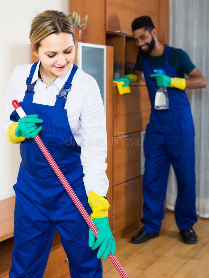 Berufspaare in der einheitlichen Reinigung am inländischen Innenraum lizenzfreie stockfotografie