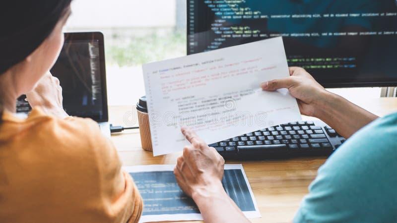 Berufsprogrammierer zwei, der an Websiteprojekt in einer Software sich entwickelt auf Tischrechner bei Firma zusammenarbeitet und stockbilder