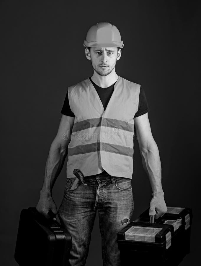 Berufsschlosserkonzept Arbeitskraft, Heimwerker, Schlosser, Erbauer auf strengem Gesicht trägt Taschen mit Berufswerkzeugen lizenzfreies stockbild