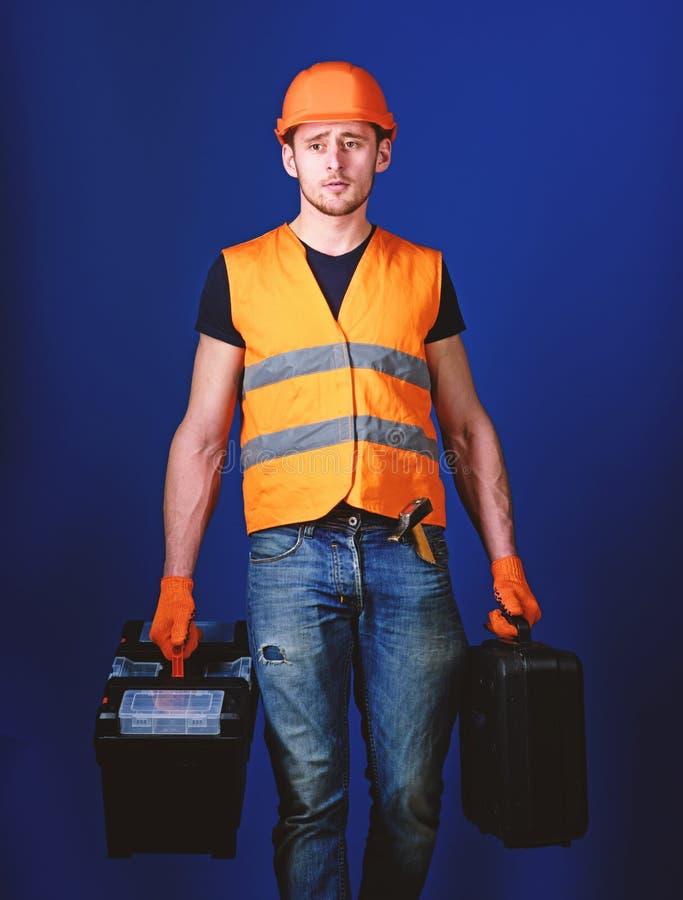 Berufsschlosserkonzept Mann im Sturzhelm, Schutzhelm h?lt Werkzeugkasten und Koffer mit Werkzeugen, blauen Hintergrund Arbeitskra lizenzfreie stockbilder