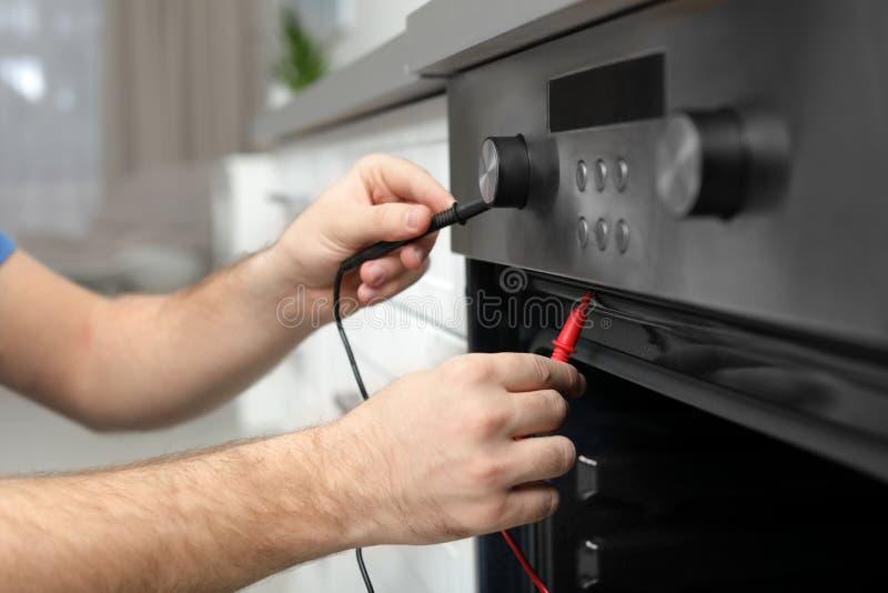 Berufssoldat, der modernen Ofen in der Küche repariert lizenzfreie stockfotos