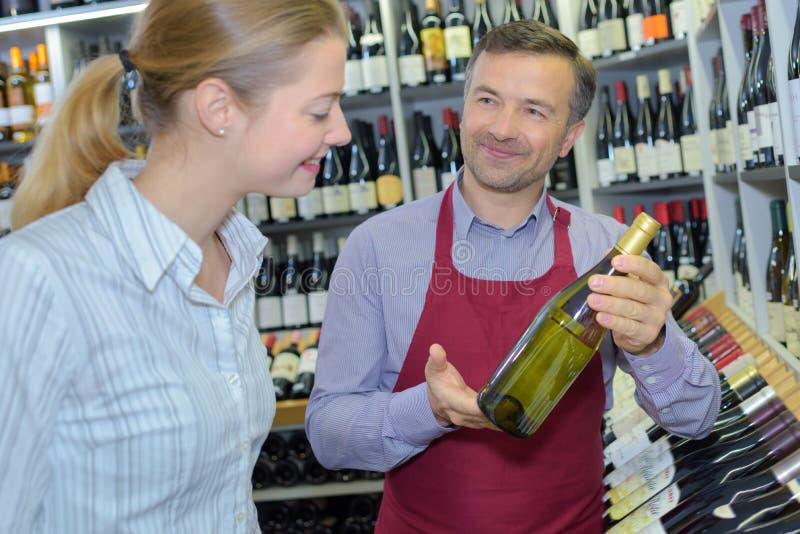 Berufssommelier, der weibliches Kundenflaschenweißwein zeigt lizenzfreie stockbilder