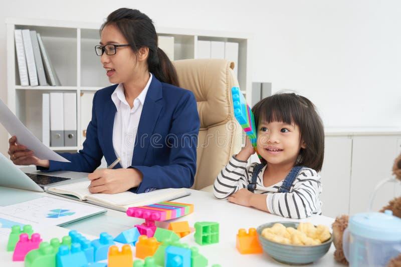Berufstätige Frau mit reizend Mädchen am Arbeitsplatz stockfoto