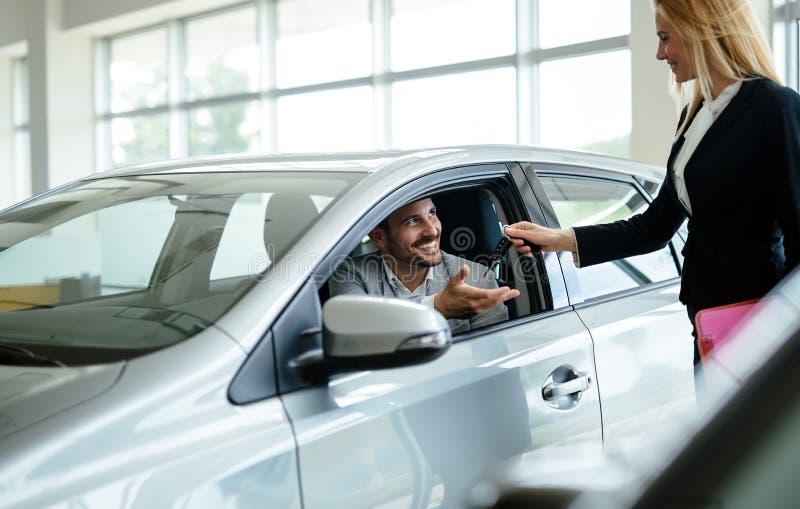 Berufsverk?ufer w?hrend der Arbeit mit Kunden am Auto-Vertragsh?ndler Geben dem Neuwageninhaber von Schl?sseln lizenzfreies stockbild