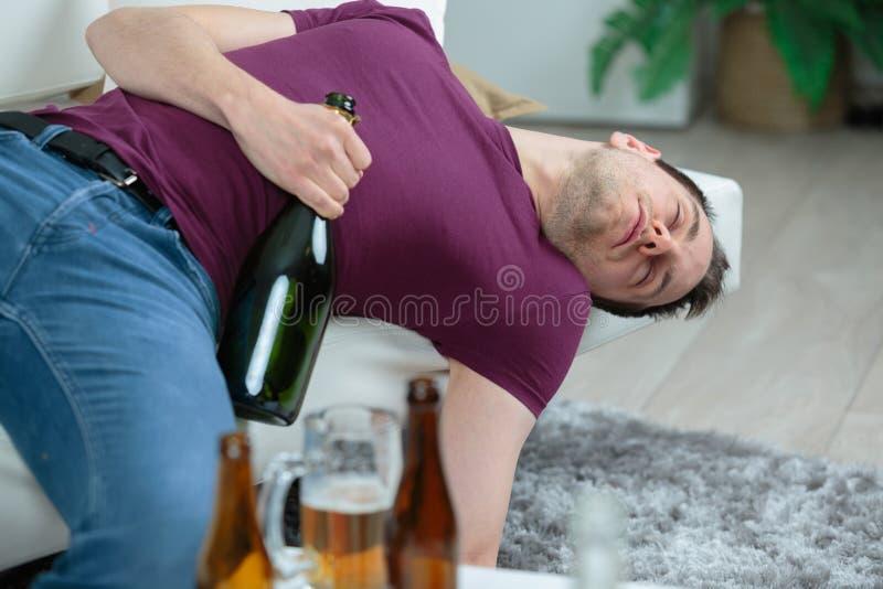 Berusad affärsman som sover med flaskvodka på soffan royaltyfri bild