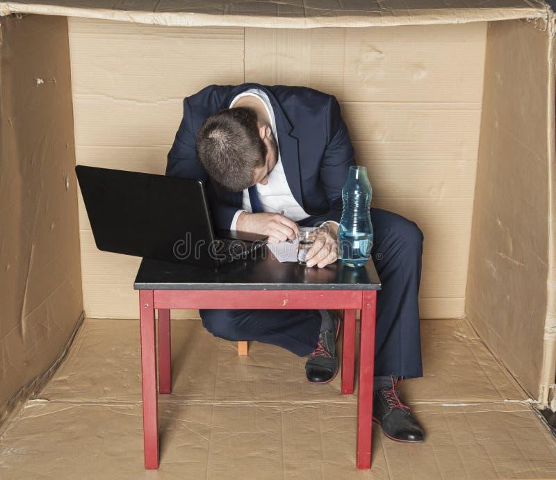 Berusad affärsman sovande på hans skrivbord arkivbild