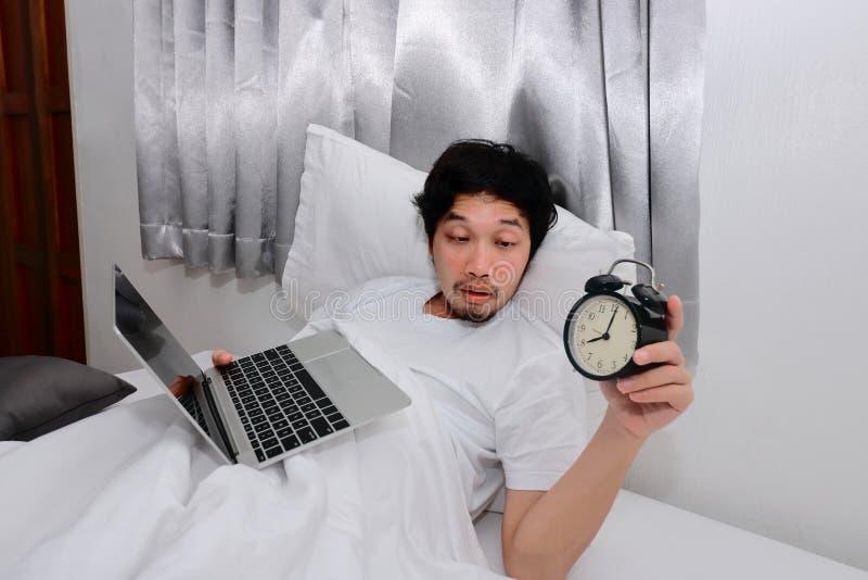 Berusad asiatisk man med bärbara datorn och ringklockan som ner ligger på sängen och har bakrus efter parti royaltyfria foton