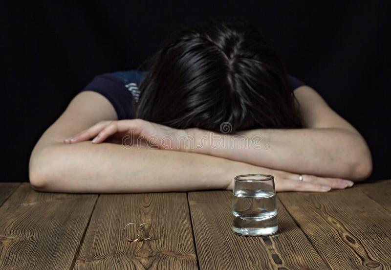 Berusad flicka och alkohol på en träbakgrund, vigselringar på en tabell, skilsmässaförbindelse royaltyfria foton