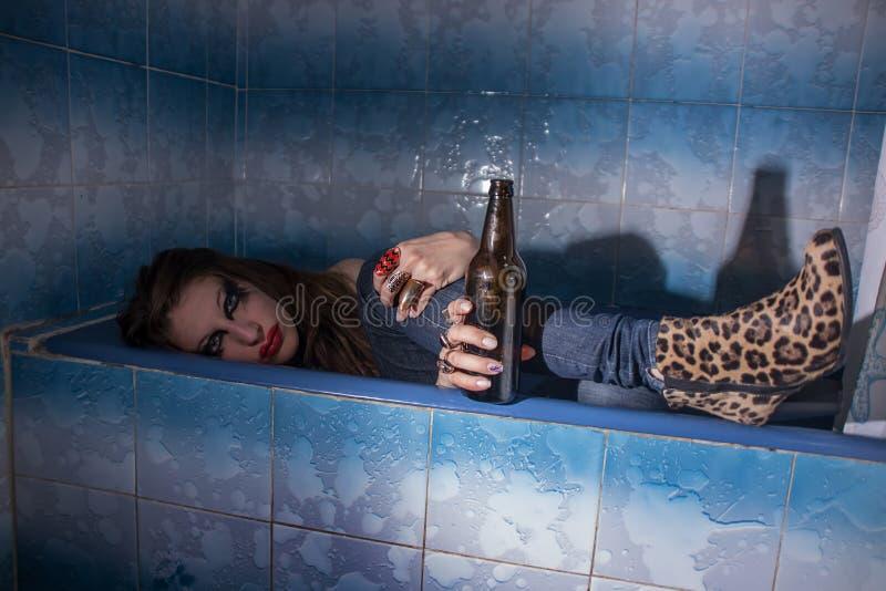 Berusad flicka som ligger i ett badkar med en flaska i hennes hand royaltyfri foto