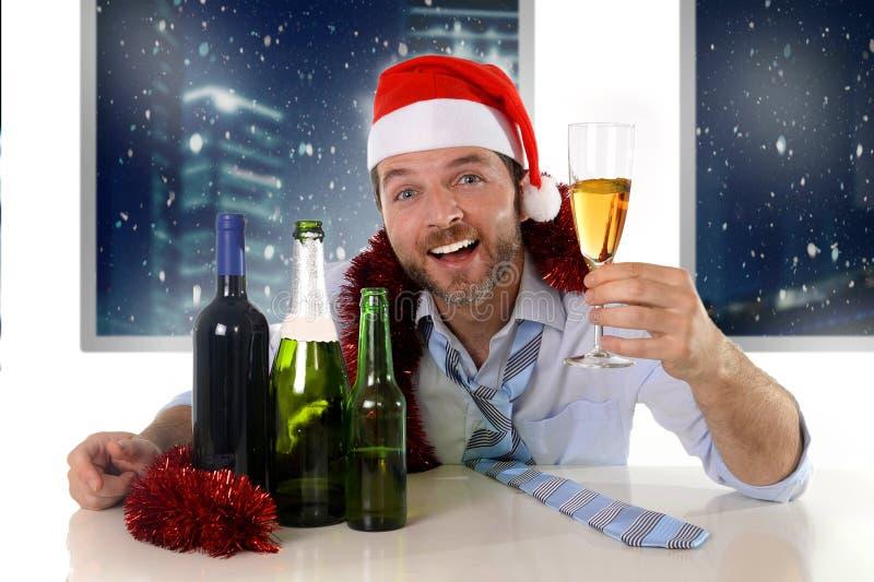 Berusad lycklig affärsman i jultomtenhatt med alkoholflaskor i rostat bröd för nytt år med champagneexponeringsglas fotografering för bildbyråer